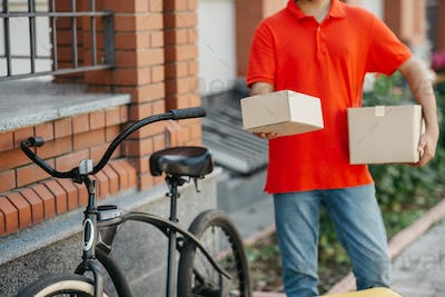 Delivery of goods to door of house. Client received parcel from courier with bicycle