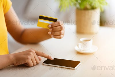 Black woman using cell phone and credit card at home