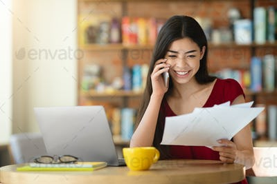 Remote Office. Asian Girl Checking Papers And Talking On Cellphone In Cafe