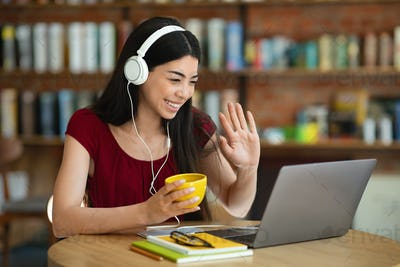 Video Call. Friendly Asian Girl In Headset Using Laptop At Cafe