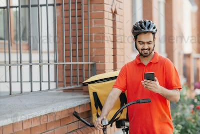 Delivery address. Smiling courier in uniform and helmet with backpack and bike watching at