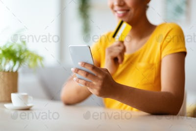Black lady using phone and credit card at home
