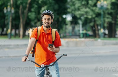 Cyclist with delivery. Happy courier with backpack, smart watch and smartphone, sits on bicycle