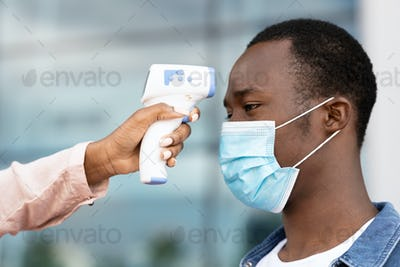 Security Checking Body Temperature With Electronic Thermomether For Black Man In Airport