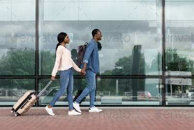 Ready for travel. Happy black couple walking with suitcases near airport building
