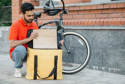 Courier and package for the client. Busy guy courier in uniform with bicycle puts goods in bag