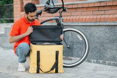 Packing the order in thermal bag. Serious guy courier with beard in uniform with bicycle looks at