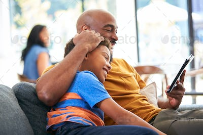 African American Family At Home With Father And Son Sitting On Sofa At Home Using Digital Tablet