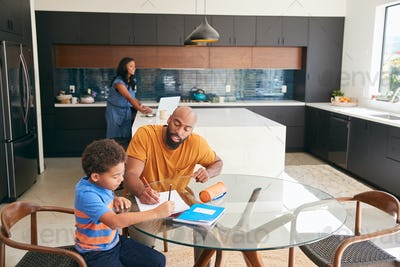 African American Father Helping Son Studying Homework In Kitchen