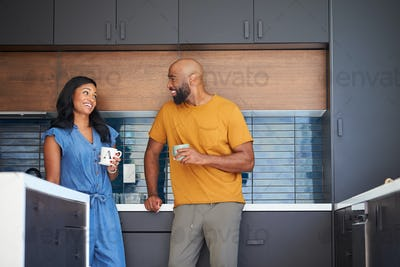 African American Couple Talking And Drinking Coffee In Kitchen At Home