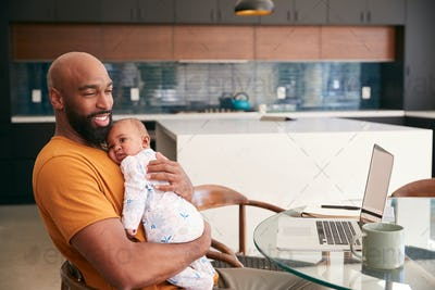 Smiling Stay At Home African American Father Cuddling Baby Daughter Whilst Working On Laptop At Home