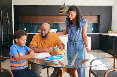 African American Parents Helping Son Studying Homework In Kitchen