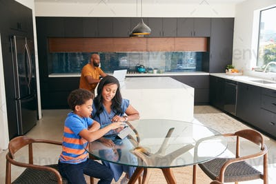 African American Mother Helping Son Studying Homework On Digital Tablet In Kitchen