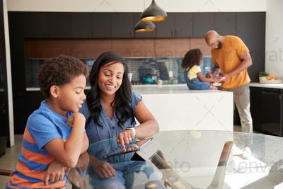 African American Parents Helping Children Studying Homework On Digital Tablets In Kitchen
