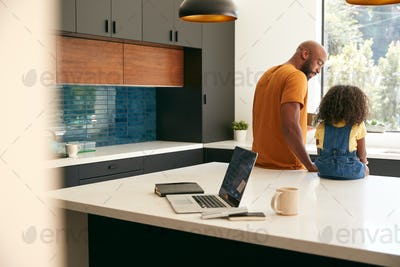 Father With Daughter Sitting On Kitchen Counter At Home Using Digital Tablet