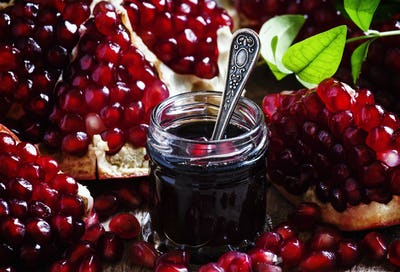 Homemade pomegranate jam in a glass jar with a spoon