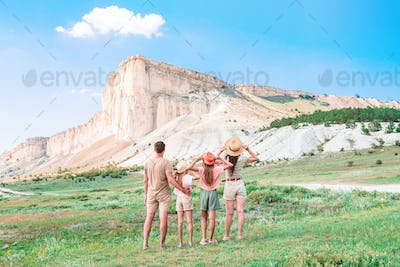 Happy family of four walking in the mountains