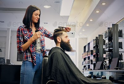 Hairdresser cutting hair of bearded male.
