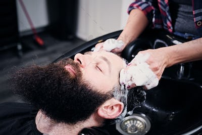 Hairdresser washing bearded men's hair.