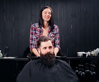 Hairdresser washing the hair of the bearded men.
