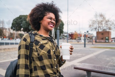 Afro american woman holding a cup of coffee.
