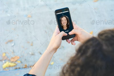 Woman unlocking smartphone with facial recognition technology