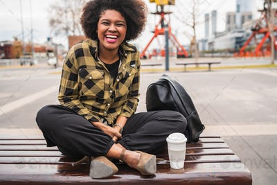 Afro american woman sitting outdoors.