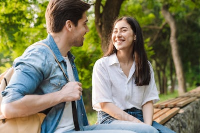 Image of couple talking and smiling at each other while sitting on bench