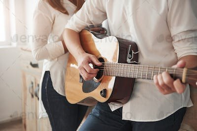 Beautiful instrument. Close up view. Guitarist playing love song for his girlfriend in the kitchen