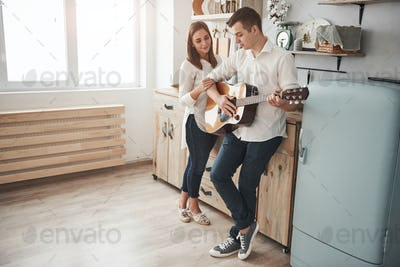 In a clean spacey room. Young guitarist playing love song for his girlfriend in the kitchen