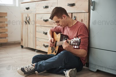 Musician plays on acoustic guitar at home in the kitchen at his weekend