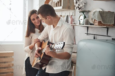 Man winning the woman. Young guitarist playing love song for his girlfriend in the kitchen