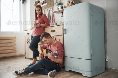 Guy sits on the floor. Young guitarist playing love song for his girlfriend in the kitchen