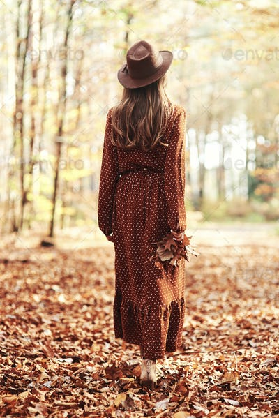 Young woman walking away with an autumnal leaf