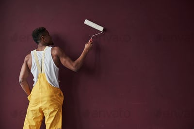 Nice velvet wall. Young african american worker in the yellow uniform have some job