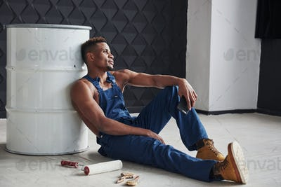 Time for the rest. African american man sits on the floor and leaning to the white barrel
