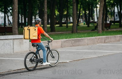 City delivery. Courier in helmet with big backpack rides on bicycle