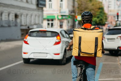 Fast bicycle courier. Delivery man in safety helmet, with bag rides a bicycle