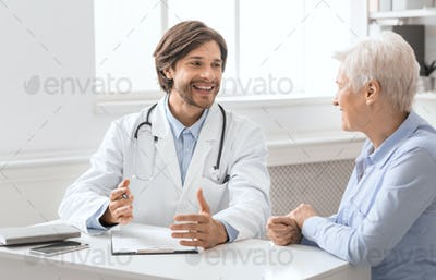 Friendly geriatrician talking with female patient, filling medical history