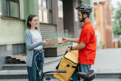 Satisfied customer receives online order. Girl takes cardboard parcel from courier with backpack and