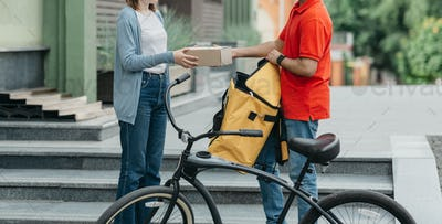 Shopaholic and online delivery. Bicycle courier with backpack and bicycle gives cardboard box to