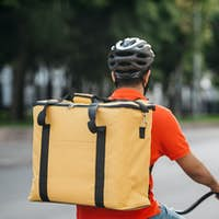 Courier in town. Deliveryman in helmet with bag rides a bicycle on road