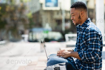 Black man using laptop, sitting in downtown with gadget