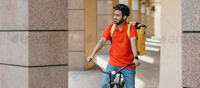 Bearded courier in helmet, in uniform and yellow backpack rides bicycle in city