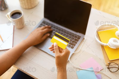 Black girl using laptop and credit card at home