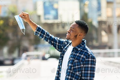 Portrait of free man taking off mask in the downtown