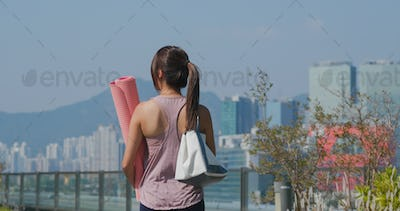 Woman hold with her yoga mat at outdoor
