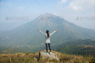 Woman standing at the peak and raising up her hand
