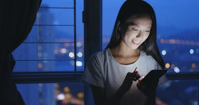 Woman working on cellphone at home