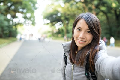 Woman holding camera for taking photo by herself